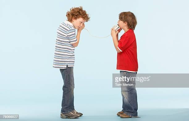 Zwei Jungen spielen mit Dosentelefon