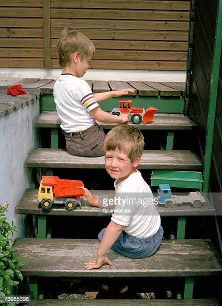 Two young boys playing with toys on steps