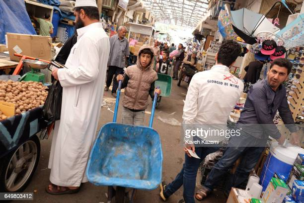 Two young boys push carts in a busy market near the citadel on November 2 2016 in Erbil Iraq Erbil also spelt Arbil or Irbil is the capital city of...