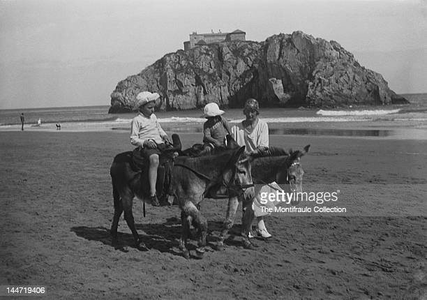 Two young boys riding donkeys on Castle Beach with their mother by their side and St Catherine's Island with its Palmerston Fort in the background...