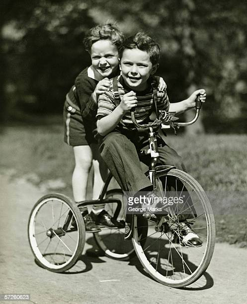 Two young boys (6-7) riding tricycle in park, (B&W), portrait