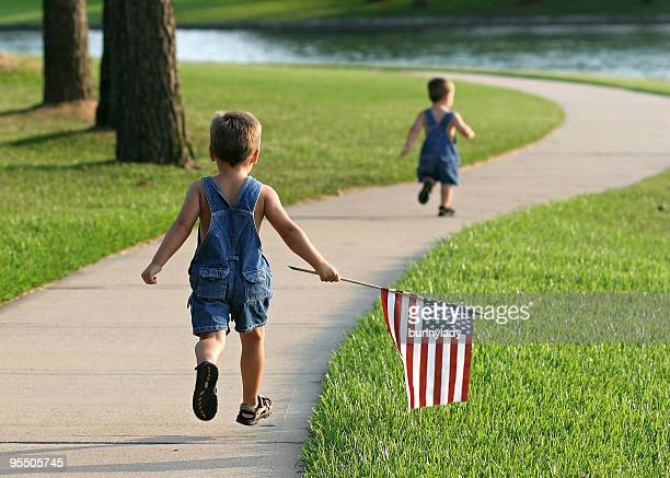 Two young boys running in a park with an American flag