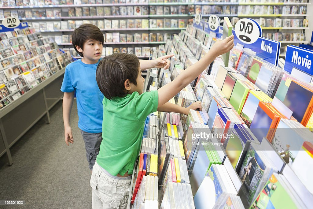 Two young boys searching for DVDs to buy