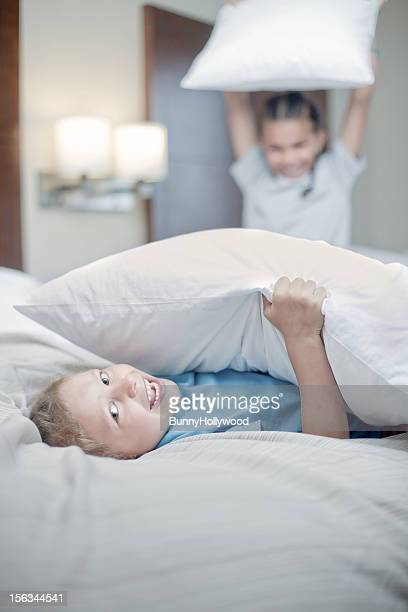 Two young boys smiling during a pillow fight