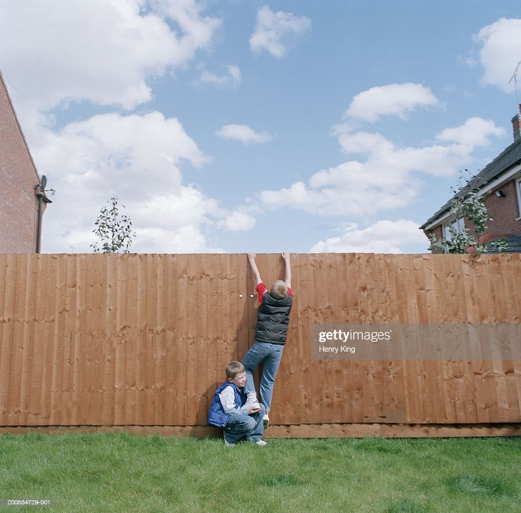 Two young boys (6-8) trying to climb over garden fence
