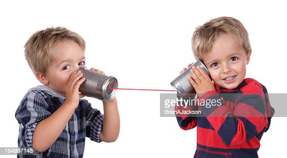 Two young boys using tin cans and a string as a telephone : Stock Photo