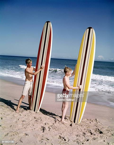 Two young boys waxing surf boards at the beach