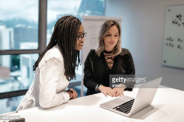 two young brazilian businesswoman looking on laptop in office