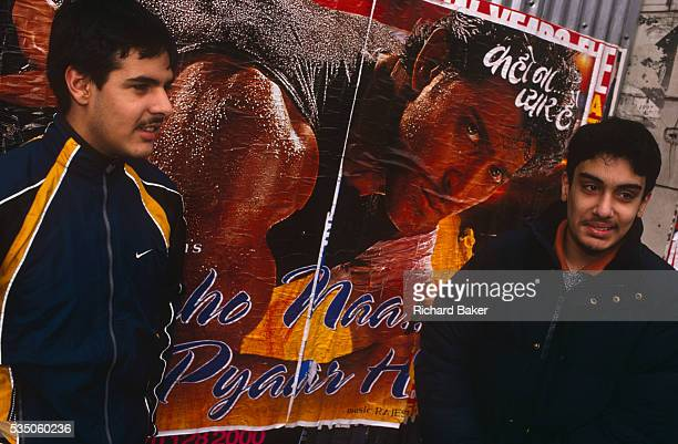 Two young British Asian men stand in front of a Bollywood action hero poster while waiting for a bus in Southhall West London England The lads are in...