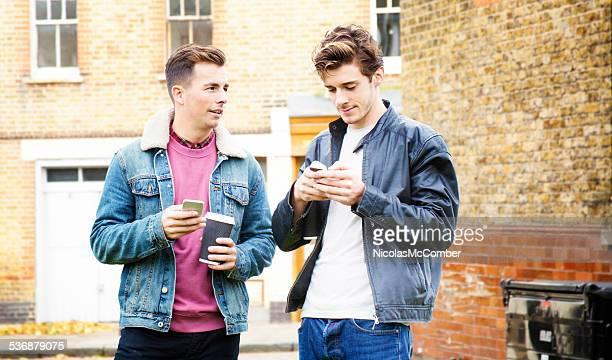 2 つの若い英国男性のソーシャルネットワークでの携帯電話の屋外