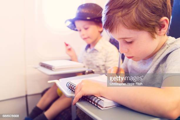 Two young brothers drawing while on an aeroplane