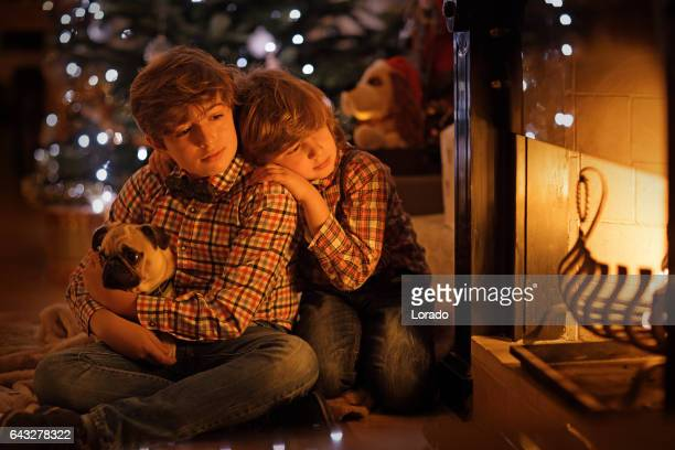 Two young brothers in christmas scene with festive decorations in indoor setting