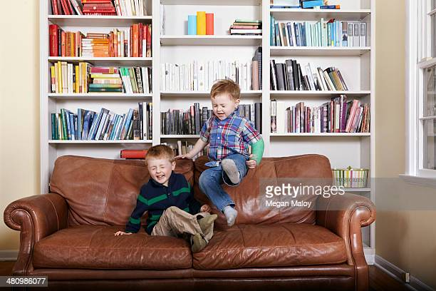 Two young brothers jumping on sofa