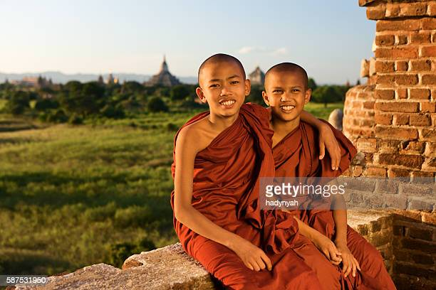 Two young Buddhist monks sitting on a stupa in Bagan