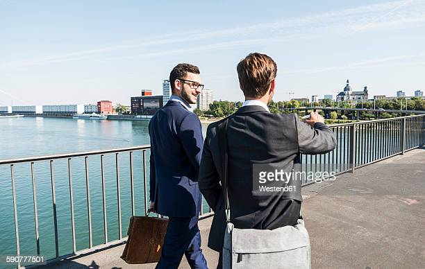 Two young business colleagues walking by river, discussing