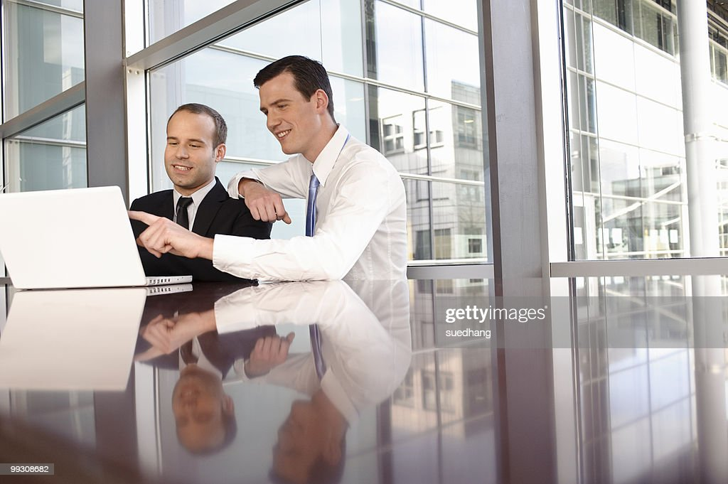 Two young business men using laptop : Stock Photo