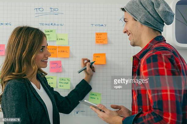 Two Young Business People Standing and Brainstorming.