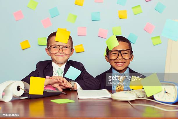 Two Young Businessmen at Desk Covered with Blank Sticky Notes