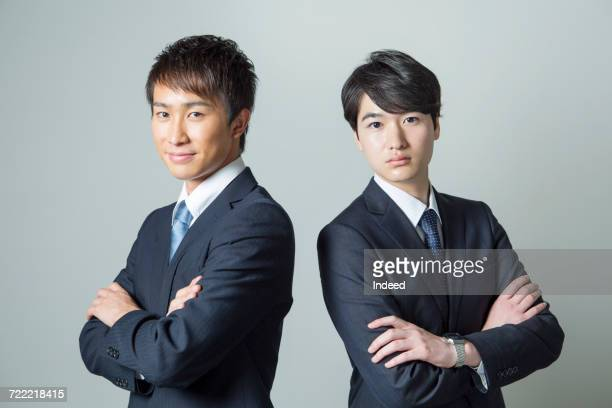 Two young businessmen crossing arms
