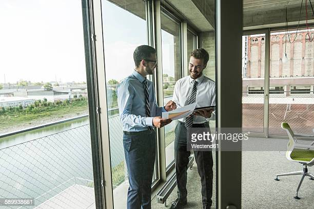 Two young businessmen looking at documents and digital tablet at the window