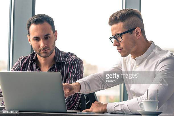 Two young businessmen making conference call on laptop in office