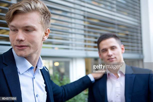Two young businessmen outdoors