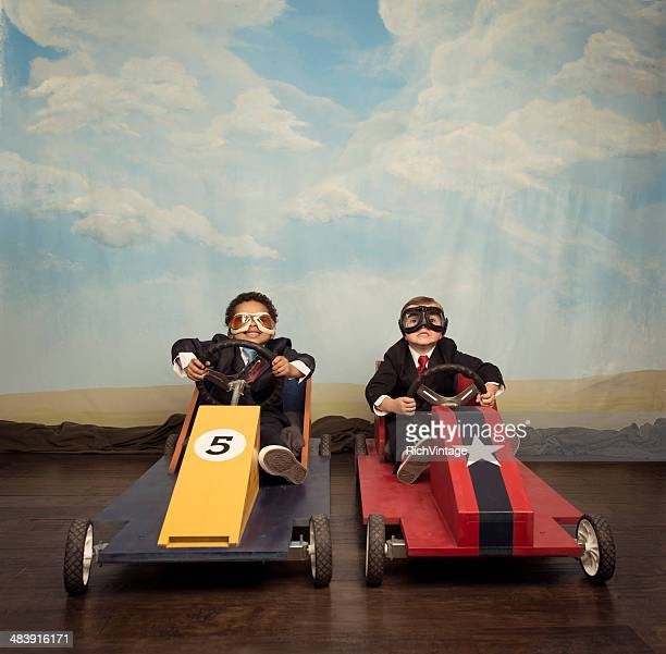 Two young businessmen race each other in toy cars