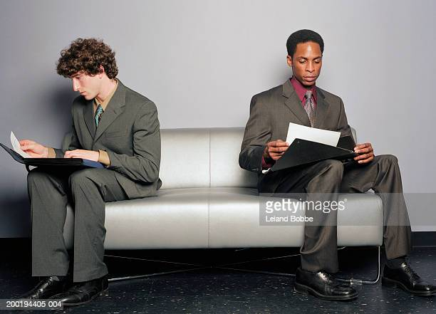 Two young businessmen reading papers