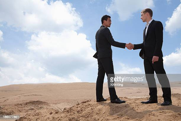 Two young businessmen shaking hands in the middle of the desert, full length