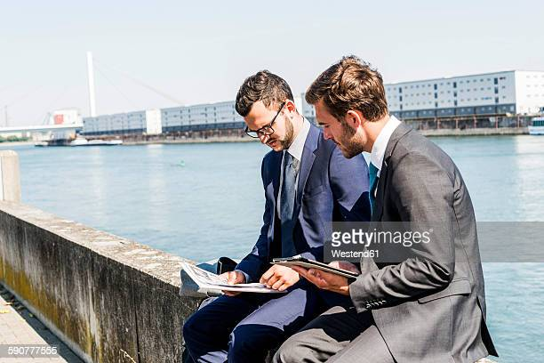 Two young businessmen sitting on wall by river, working