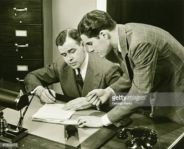 Two young businessmen talking at small desk, (B&W)