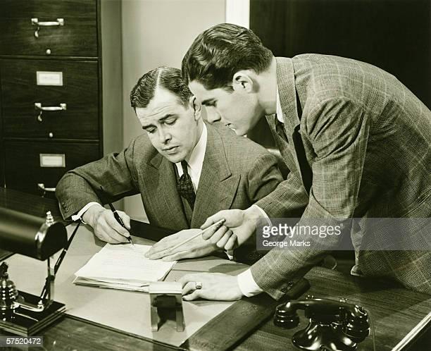 Zwei junge Geschäftsleute sprechen im kleinen Schreibtisch, (B & W