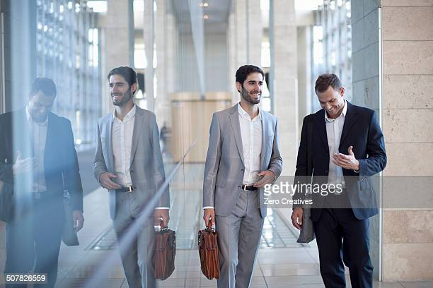 Two young businessmen walking and chatting in conference centre
