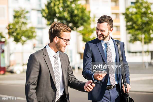 Two young businessmen walking in city, looking at mobile phone