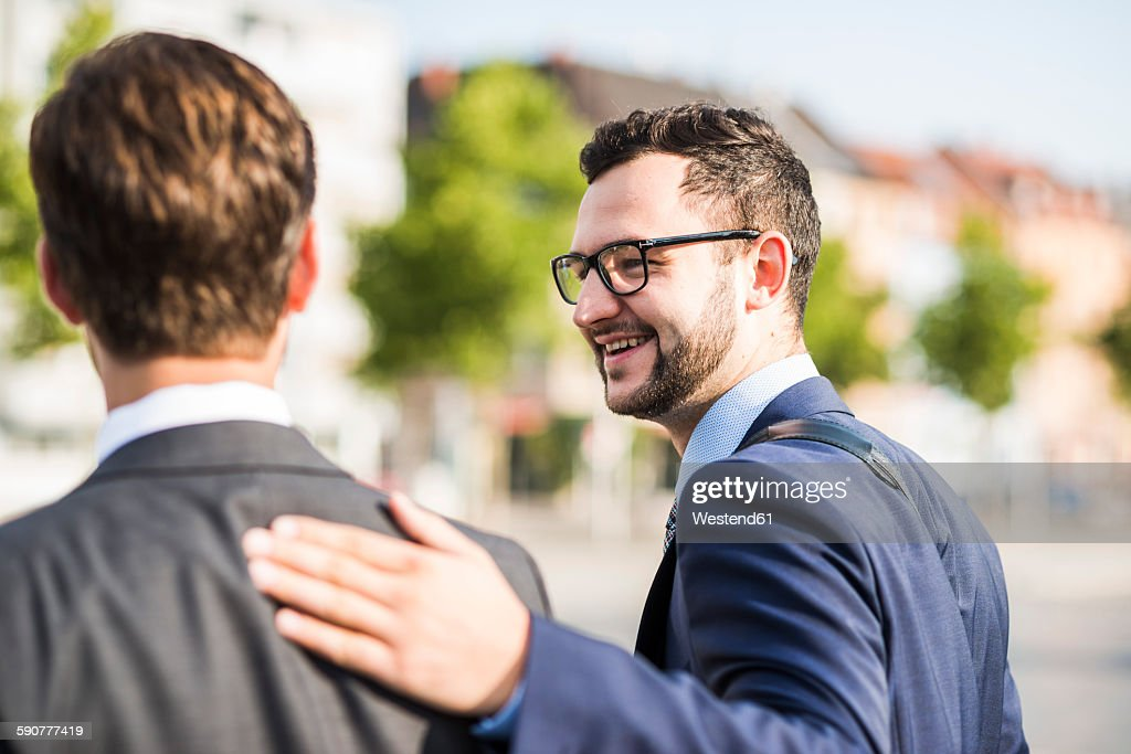 Two young businessmen walking in city, one patting colleagues back