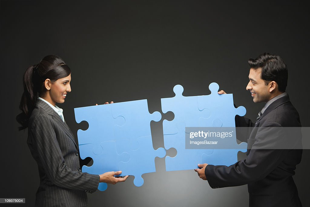 Two young businesspeople adjusting large blue jigsaw pieces : Stock Photo
