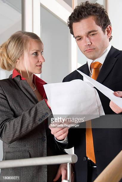Two young businesspeople looking over and discussing documents