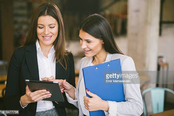 Two young businesswomen discussing business strategy using digital tablet