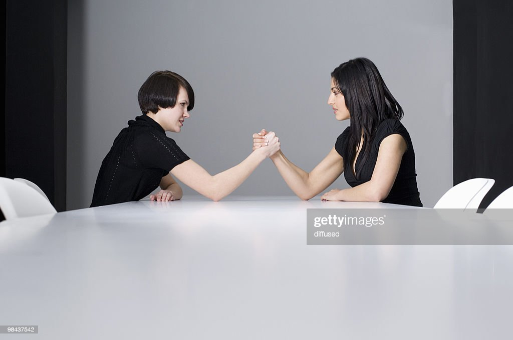 two young businesswomen doing arm wrestling at conference table : Stock Photo
