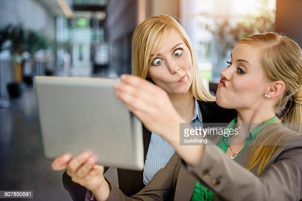 Two young businesswomen pulling faces and taking selfie on digital tablet in office