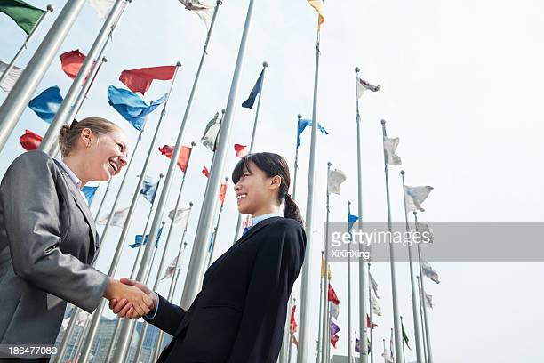 Two young businesswomen shaking hands outdoors