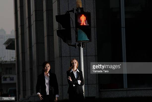 Two young businesswomen standing by traffic lights