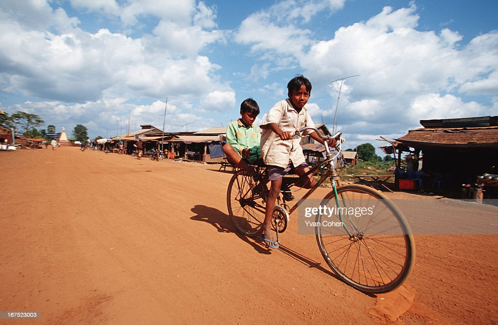 Two young Cambodian boys bicycle along a dusty main avenue in Anlong Veng, a former stronghold of the Khmer Rouge that is now opening up to travellers..