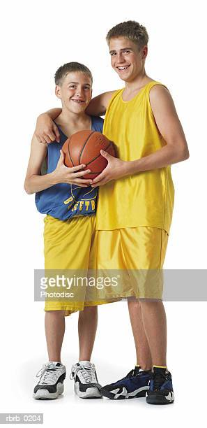 two young caucasian brothers in yellow and blue basketball uniforms hold the ball as one puts his arm around the other