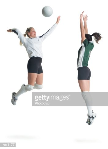 two young caucasian female volleyball players from opposing teams square off as one jumps and hits the ball while the other prepares to block