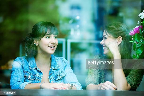 Two Young Cheerful Female Friends Sitting in a Bar