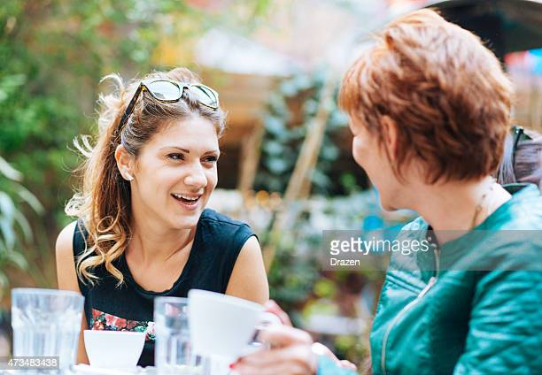Two young cheerful women having afternoon coffee break in restaurant