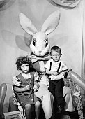Two young children in the embrace of the Easter Bunny 1950
