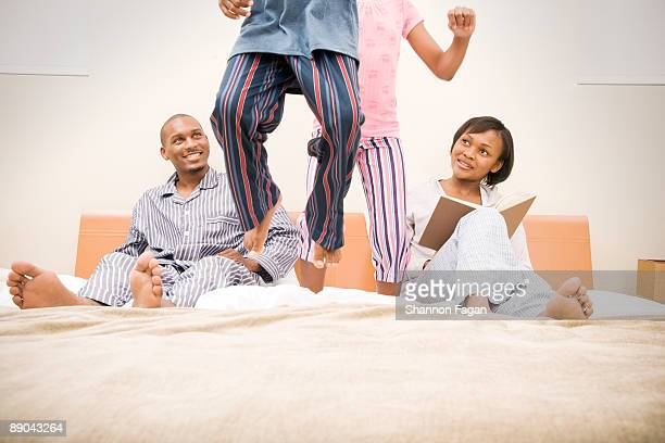 Two Young Children Jumping on Parents' Bed