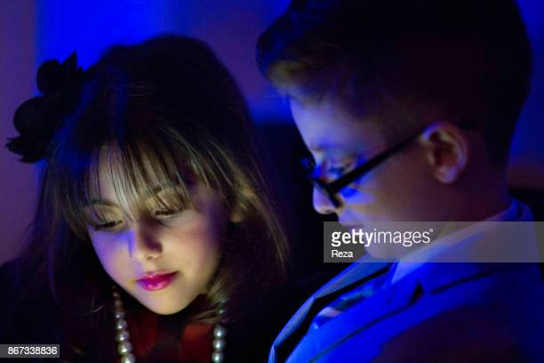 Two young children look at an Ipad during an Easter party gathering of the Assyrian families to celebrate Easter in the big lounge of the...
